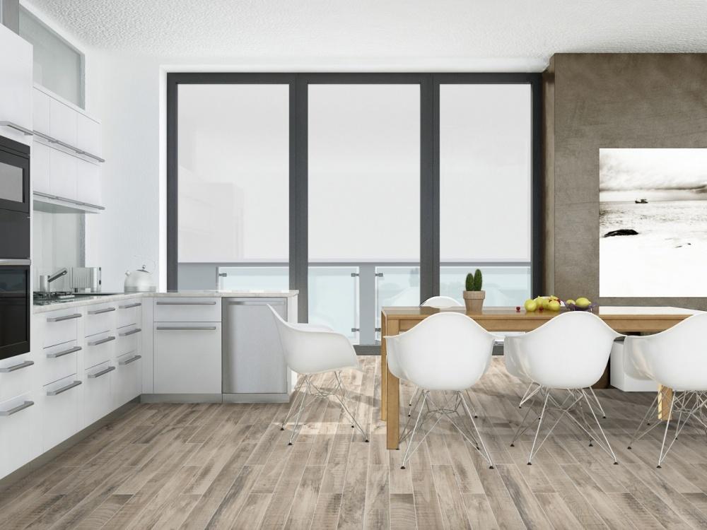 Miljöbild över kök med ljus inredning, träbord och stolar. På golvet ligger en ljus träklinker.