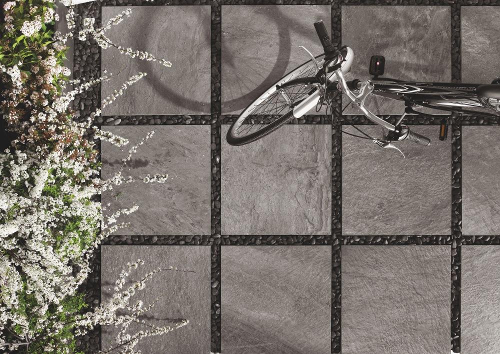 Bild tagen uppifrån över grå granitkeramikplattor med stenlook som lagts i grus. På dem står en cykel.