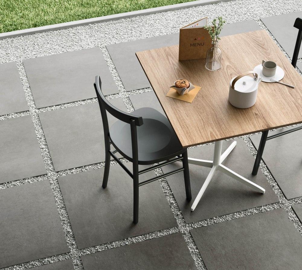 Miljöbild på cafébord och stolar som står på gråa keramikplattor.