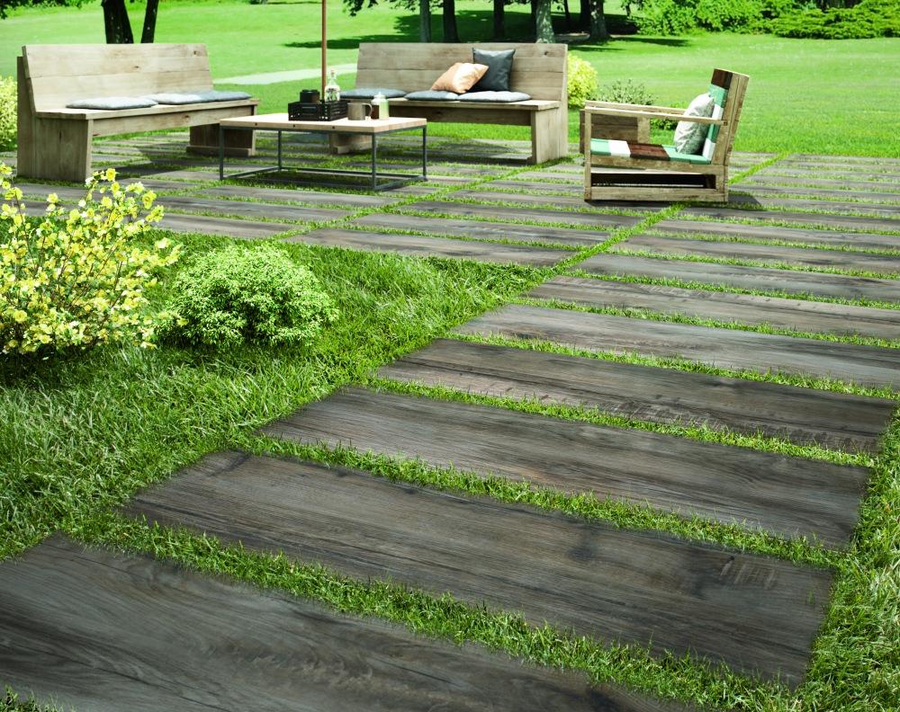 Miljöbild på trädgård där plattor med träbock lagts på gräs. På dessa står utemöbler.