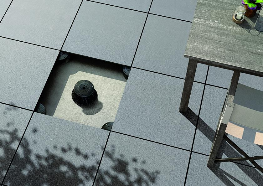 Bild tagen uppifrån på en uteplats med mörkgrå granitkeramikplattor.