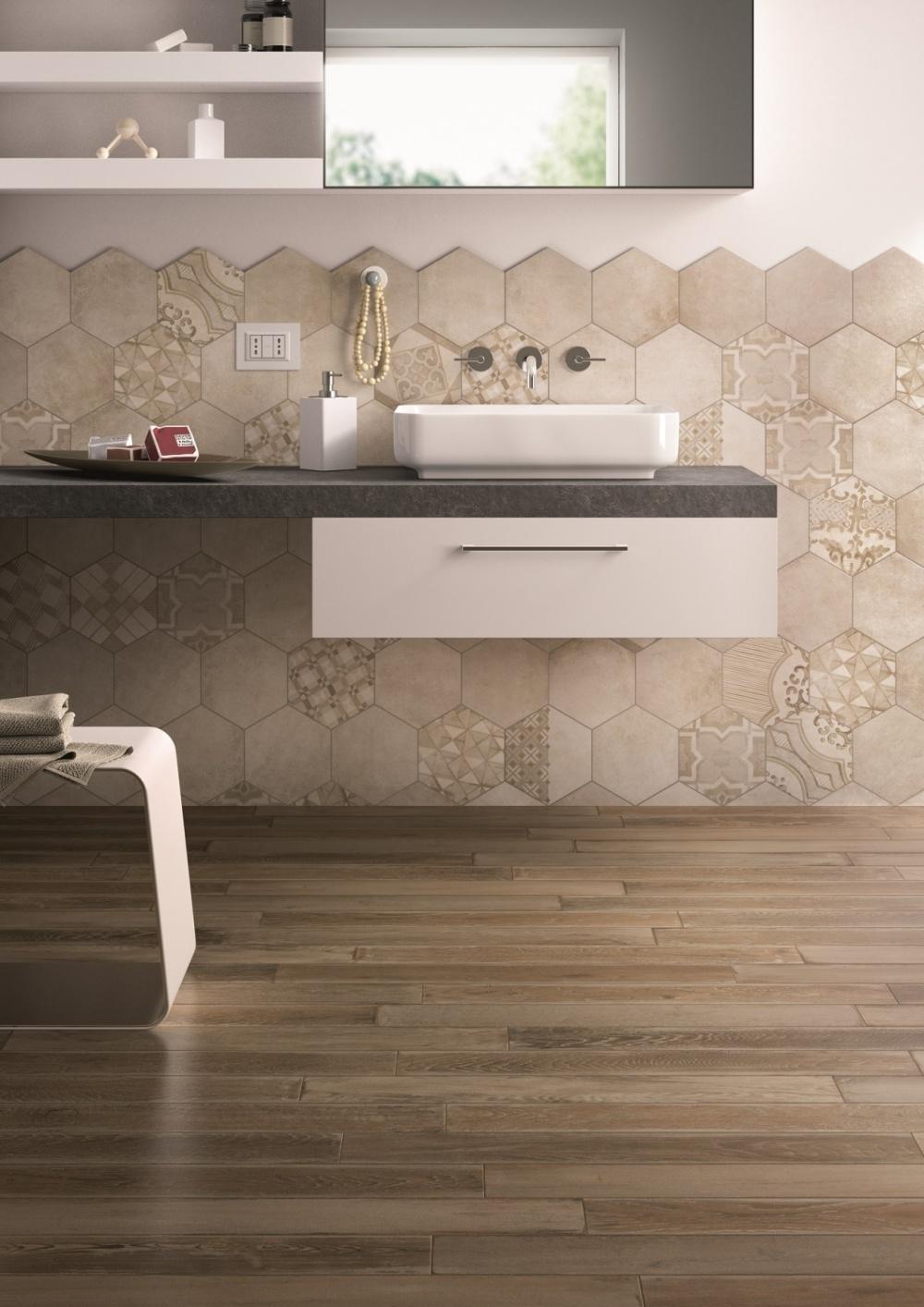 Badrum som går i beige toner. På väggen finns en badrumsmöbel och ett handfat. På golvet ligger en mörk träklinker.