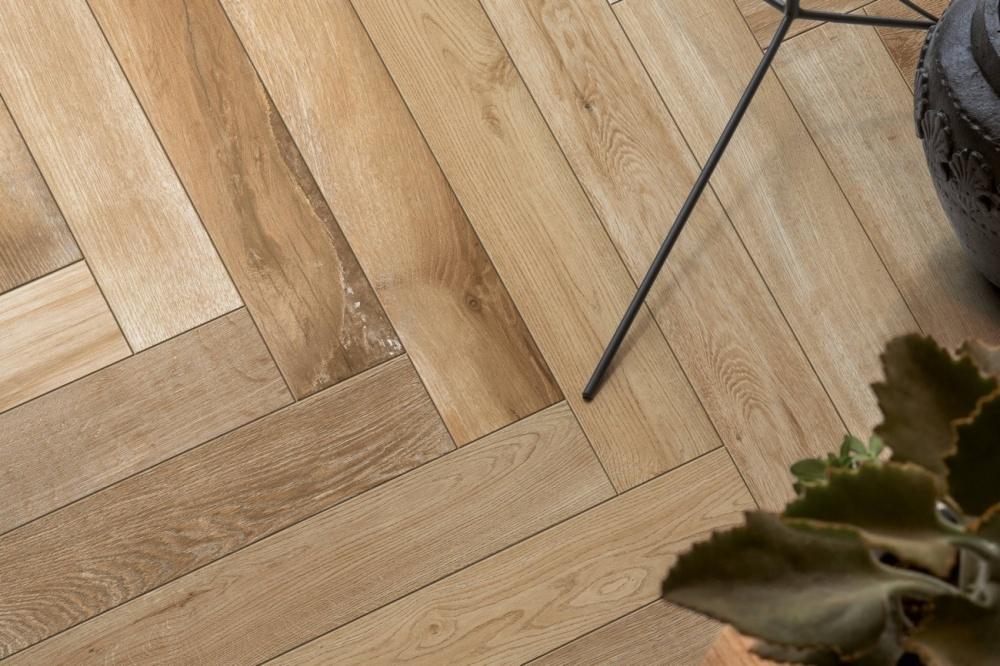 Bild på ett golv tagen uppifrån. En ljus träklinker lagd i fiskbensmönster.