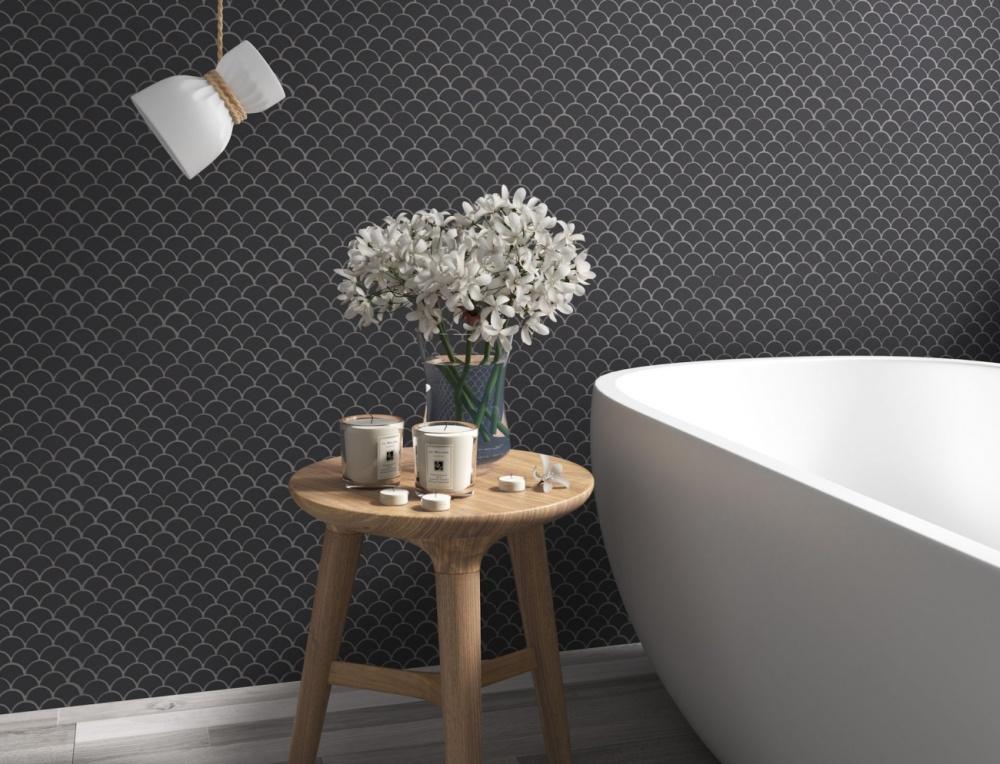 Badrum med mörkt grå fiskfjällsmosaik i kontrast mot ett vitt badkar med runda former. Det syns även en träpall med blommor och ljus på.