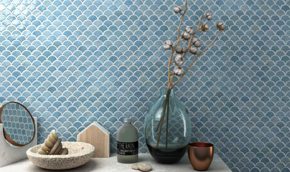 En vägg med blå fiskbensmosaik. Framför väggen syns bland annat en vas och en liten spegel.
