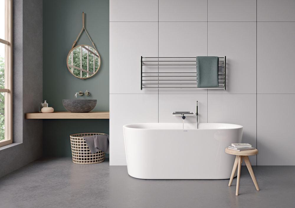 Badrum med grått golv och vit vägg. På väggen sitter en handdukstork nedanför vilken ett badrum står.