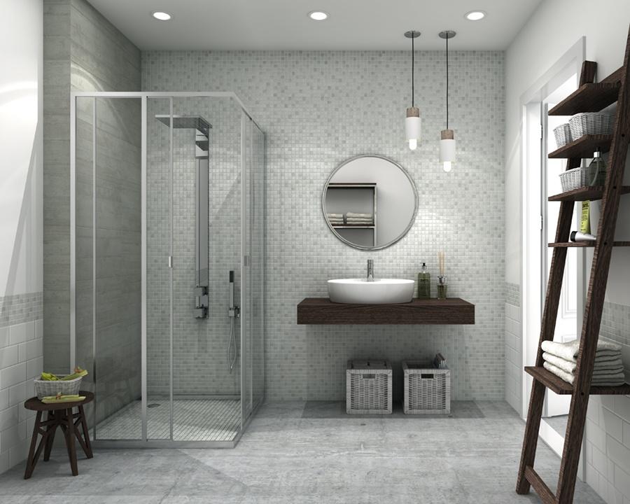 Miljöbild på badrum i olika grå toner på både golv och väggar. Rakt fram syns en duschhörna, en rund spegel och ett handfat.