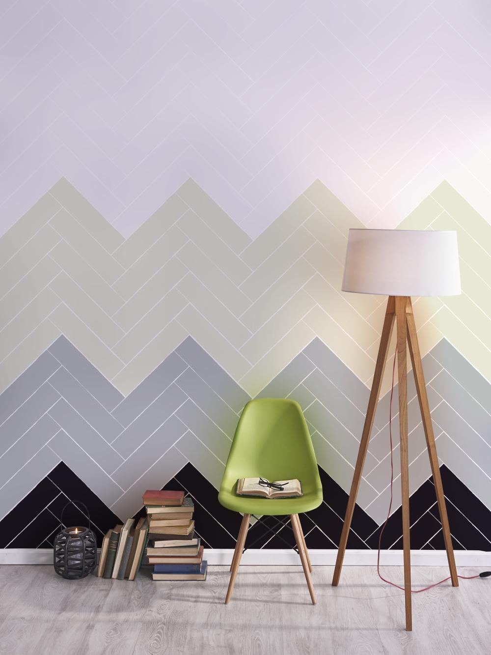 En stol och en lampa står framför en vägg med långsmala plattor i olika färger. Plattorna är satta i fiskbensmönster.