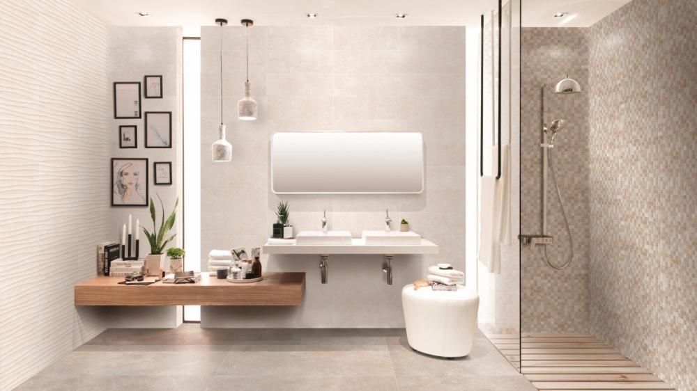 Miljöbild över badrum med beige plattor på väggar och golv. Rakt fram är två handfat och en stor spegel och till höger en duschhörna.