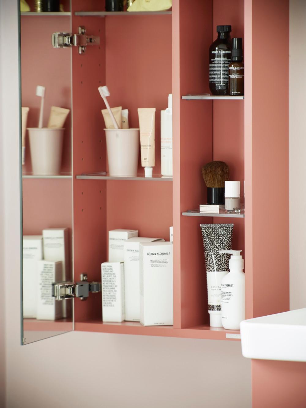 Badrumsskåp i persikofärg. Spegeldörren är öppen och det står krämer, tandborstar och annat på hyllorna.