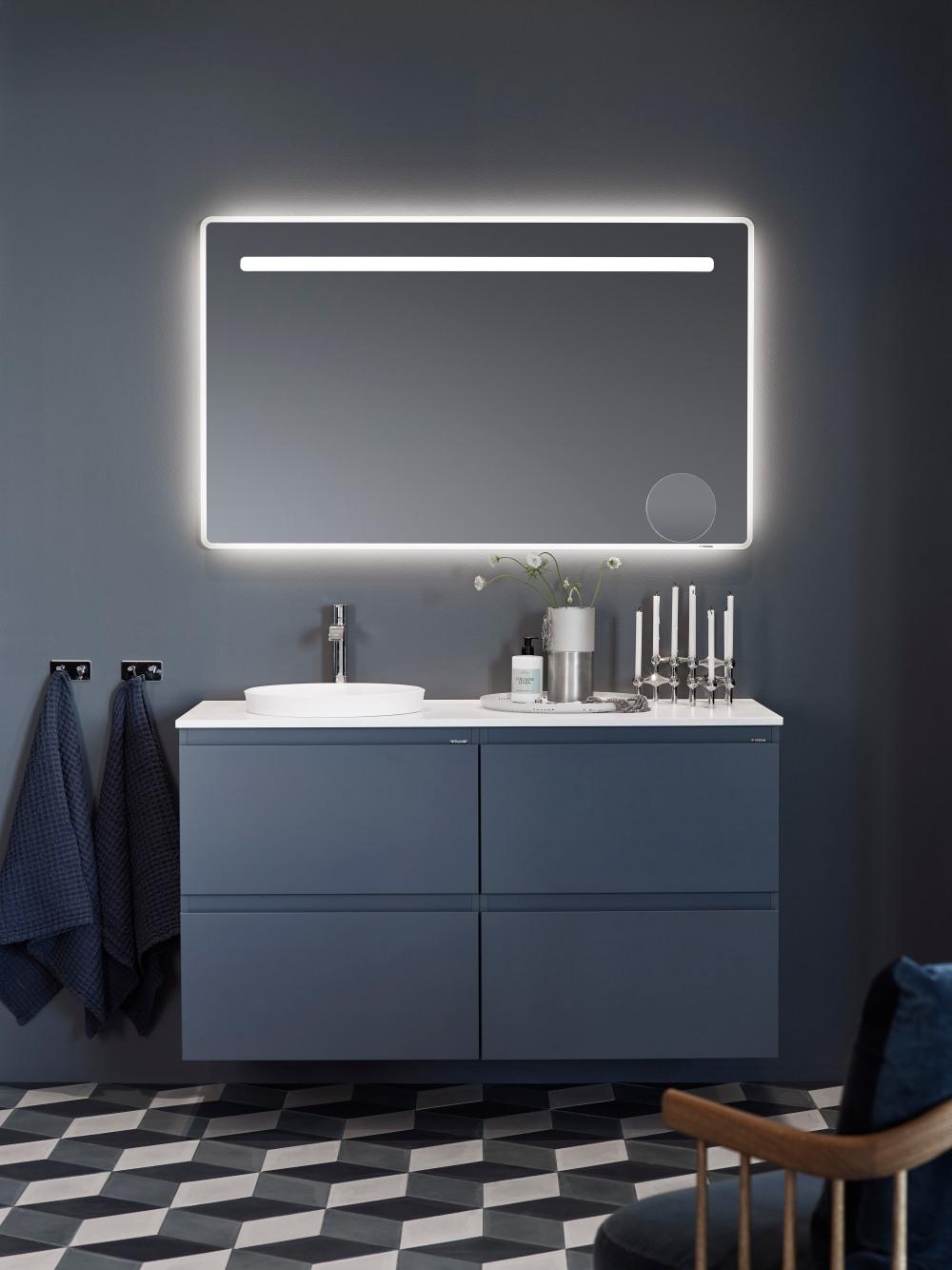Bild på blått badrumsskåp med handfat och spegel.
