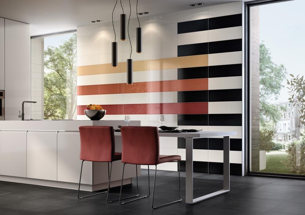 Miljöbild över kök med två röda stolar vid ett högt bord. På väggen sitter avlånga plattor i vitt, svart, rött och gult.