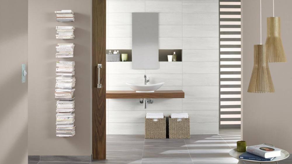 Miljöbild över badrum med ljust beige väggplattor och detaljer i trä.