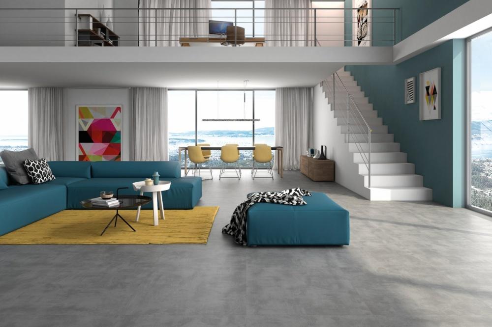 Miljö med två våningar. Golvet är grått och det finns en blå soffa och en gul matta.