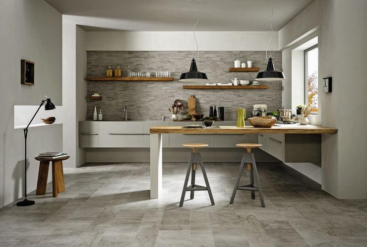 Miljöbild tagen rakt framifrån över ett kök. Bortre väggen har öppna hyllor upptill och vita skåp nedtill. Det finns ett högt bord med barstolar. Golv och vägg har grå plattor .
