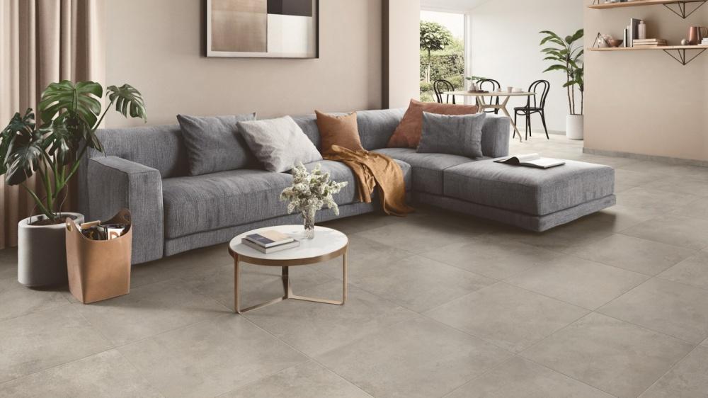 Vardagsrum med grå plattor i 60x60 cm på golvet. I bild syns också en mörkgrå soffa med kuddar och ett soffbord