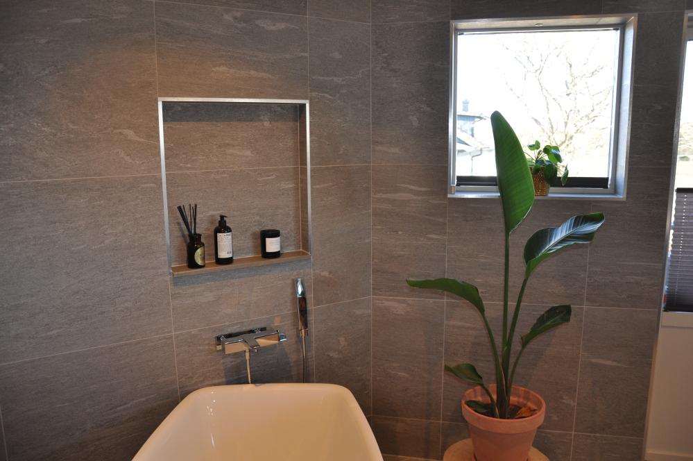Överblicksbild på badrum. I botten av bilden syns kanten av ett badkar, ovanför badkaret en infälld hylla med en pumpflaska, doftpinnar och ett ljus. Till höger är det ett fönster under vilket det står en grön växt.