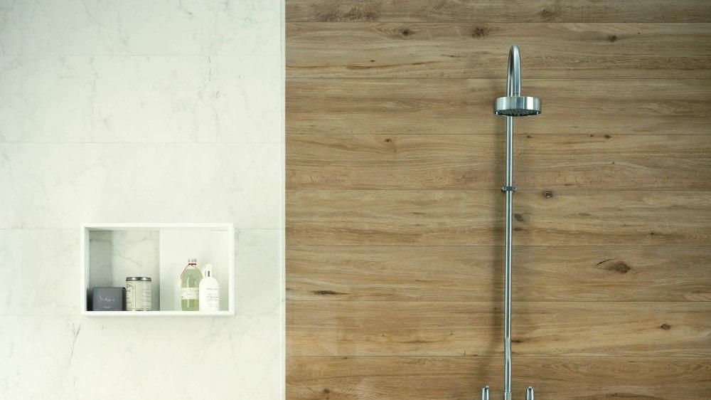 Bild från duschvägg, till hälften med marmorplattor och till hälften med träklinker. Till vänster en infälld hylla med tvål och liknande.