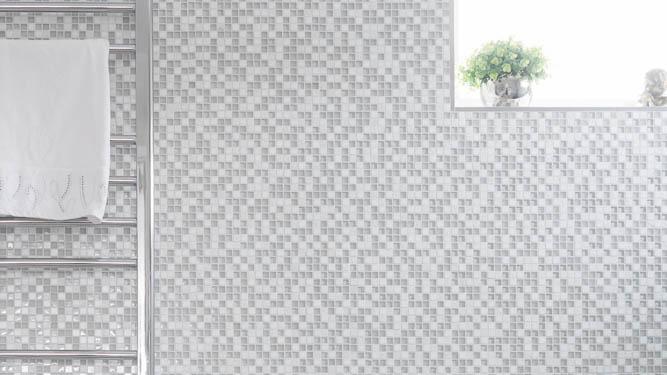 Bild från badrum med mosaik i olika grå nyanser. Till vänster hänger en silverfärgad handdukstork och i högra hörnet syns delar av ett fönster med en liten växt i.