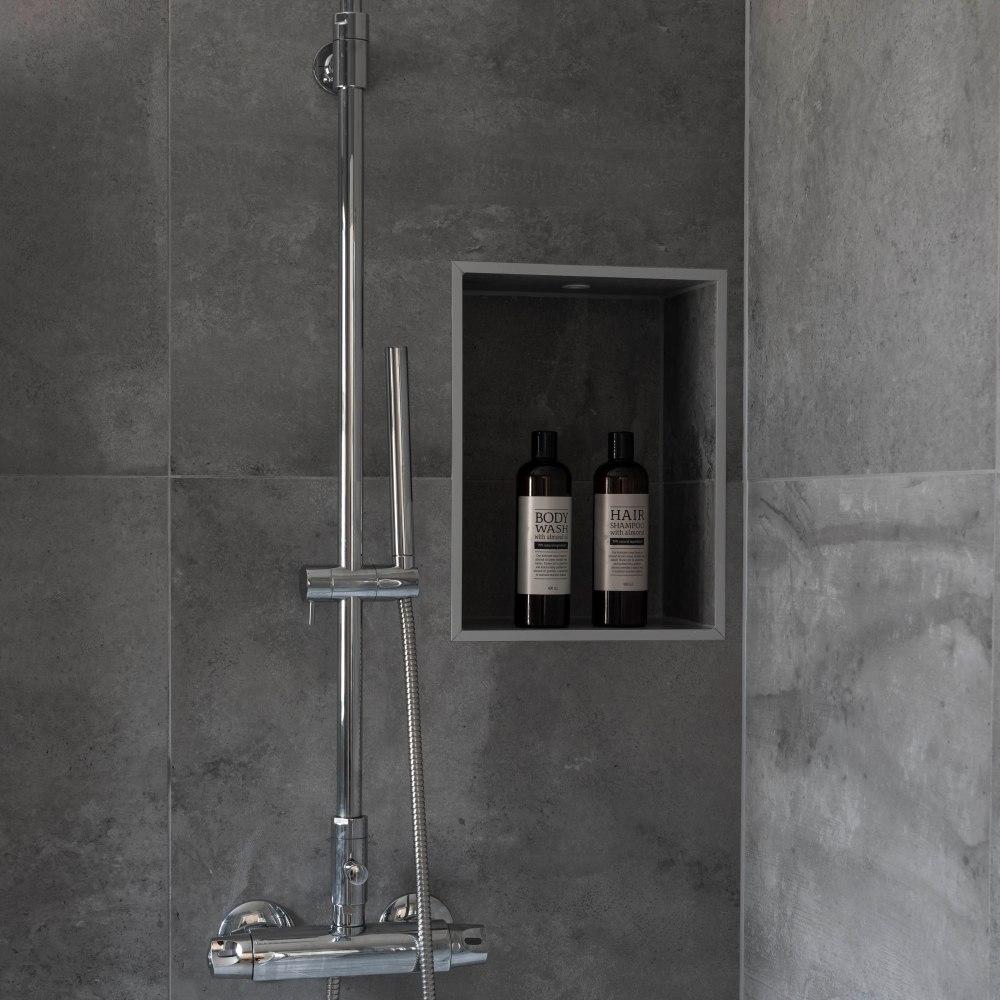 Duschhörna med blank blandare och en infälld hylla. I hyllan står schampoo och duschkräm. Plattorna är grå och skiftande i nyans.