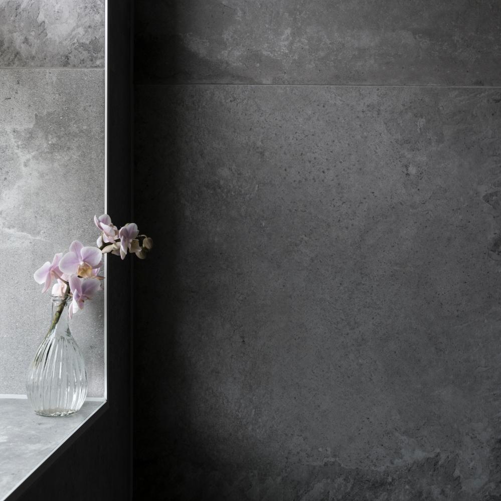 Detaljbild från badrum. Till vänster en fönsternisch i vilken det står en glasvas med en orkidékvist i. Bilden är ljusare till vänster där fönstret är och mörkare till höger som är inåt rummet.