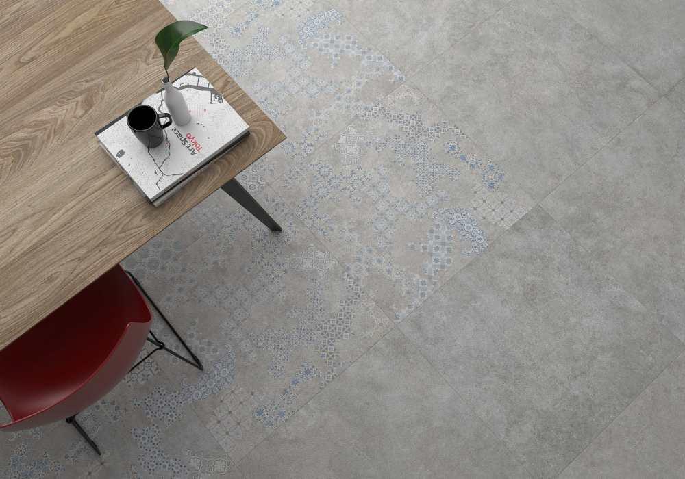 Vy snett ovanifrån. Grått golv som delvis är mönstrat i diskreta färger. I vänstra kanten syns ett bord och en röd stol.