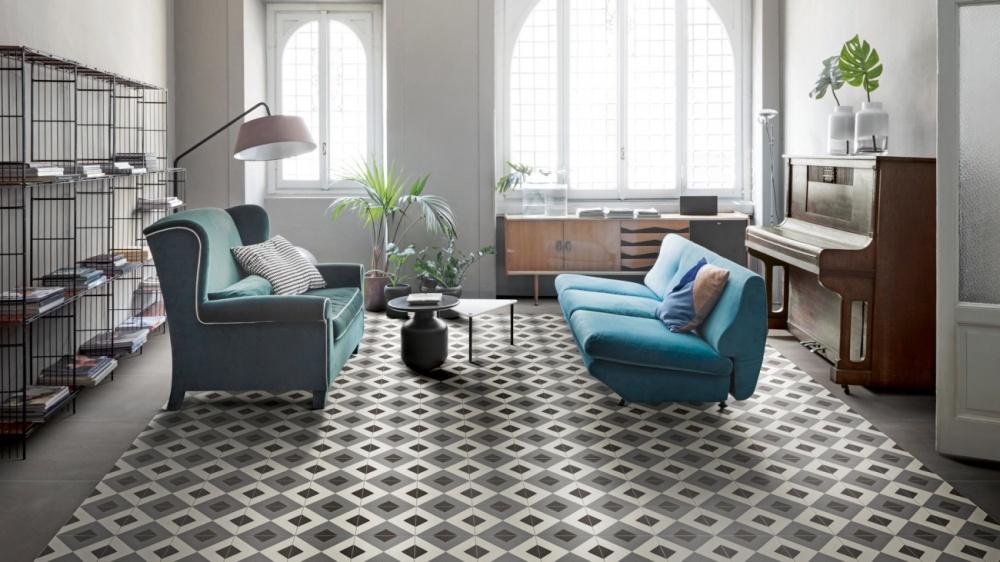 Vardagsrum sett från sidan. Mönstrade plattor på golvet, färgglada soffor, växter och stora fönster längst bort i bild