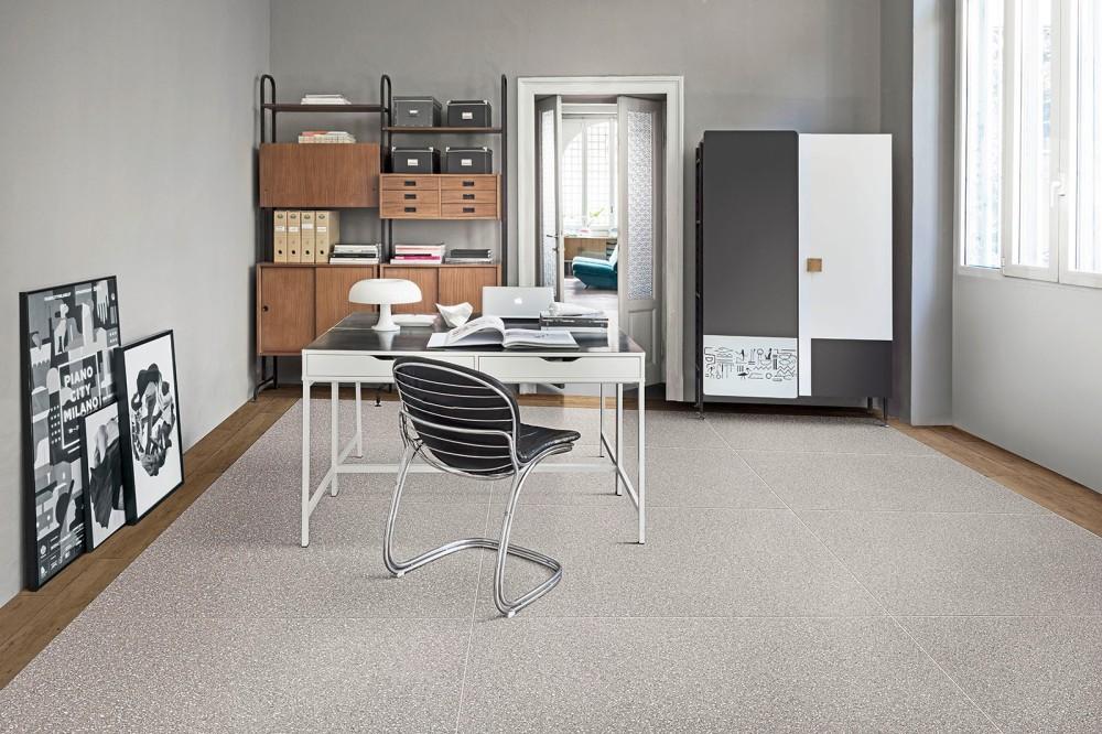 Arbetsrum med skrivbord och stol samt hyllor. På golvet ligger terrazzoplattor och längs med golvets kanter ligger träklinker.
