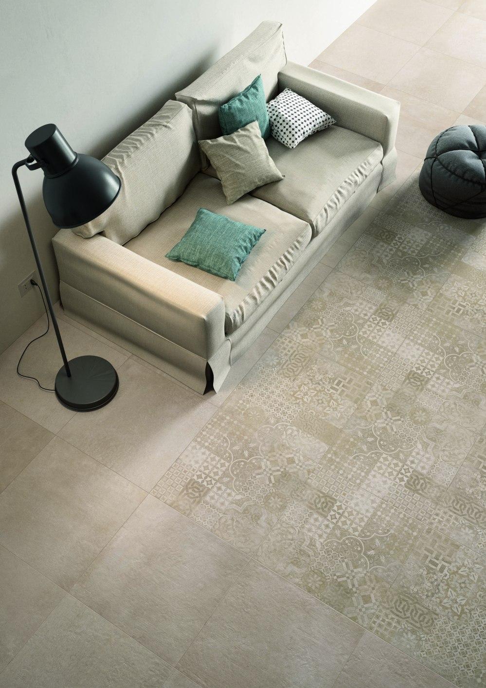 Bild tagen snett utifrån. Beige golv där en del av golvet har mönstrade plattor i samma nyans. Det finns en beige soffa och en svart lampa.