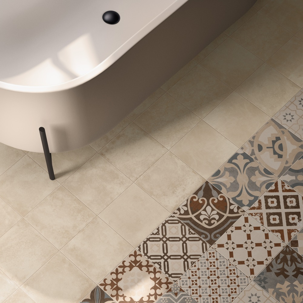 Vy ovanifrån med ett badkar i överkanten. Golvet är i huvudsak beige men i högra hörnet bryter mönstrade plattor i beige nyanser av.