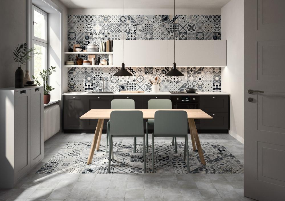 Kök med bord och fyra stolar och en vägg med köksskåp och arbetsyta. På en del av golvet och bortersta väggen ligger och sitter mönstrade plattor i olika grå och beige nyanser.