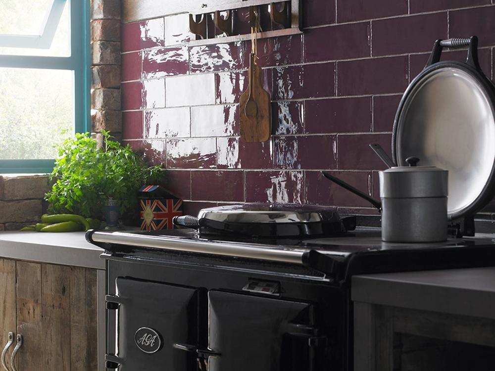 Köksmiljö med en spis framför en vägg kaklad med vinröda plattor.