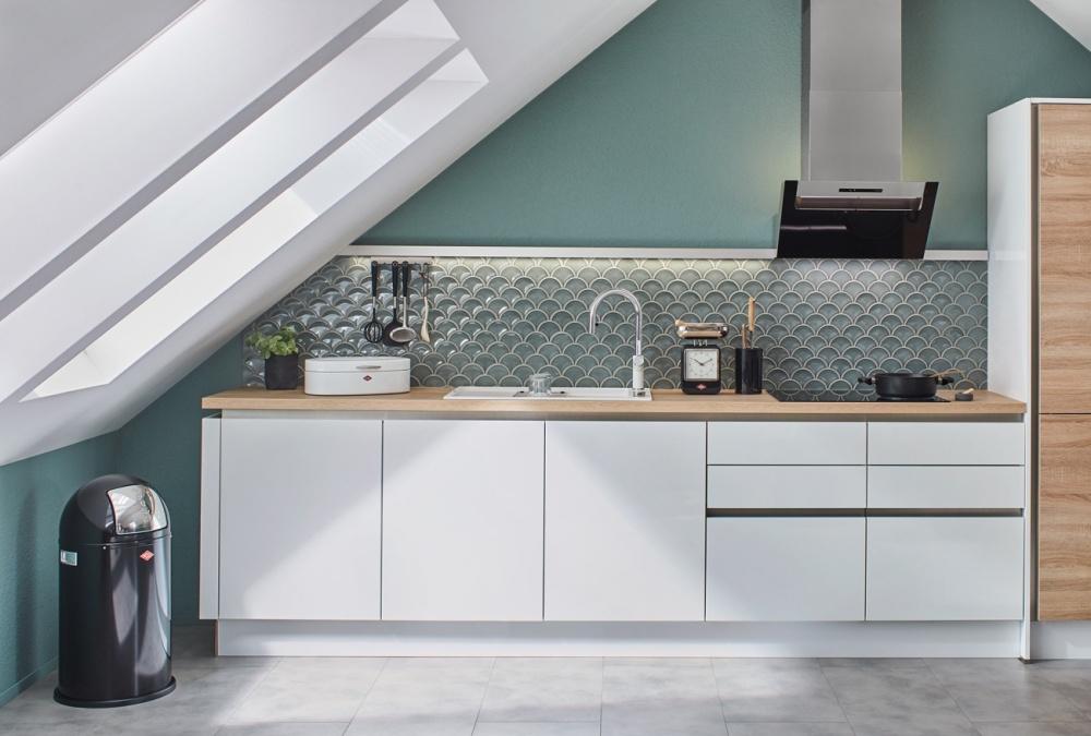 Bild från kök med snedtack till vänster. Vita skåpsluckor nedtill, petrol-färgad vägg upptill. Petrol-färgad mosaik i fiskfjällsformat som stänkskydd.