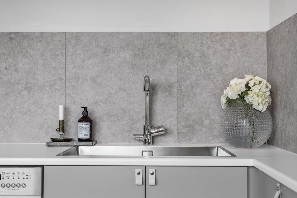 Bild från kök, grå kökslucokor, en diskho och blandare, på väggen grå plattor med stenlook.