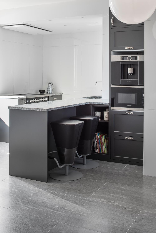 Bild på kök. Blå plattor med stenlook på golvet, köksö med barstolar och köksmaskiner till höger. Väggar med vita blanka plattor.
